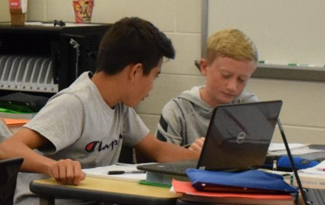 From left: freshman Justin Williams and Sean Elster work together on laptops during their math class.