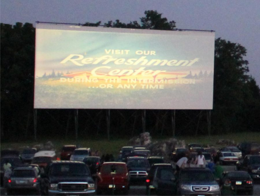 Cars line up and wait for a movie to start at a drive-in theater