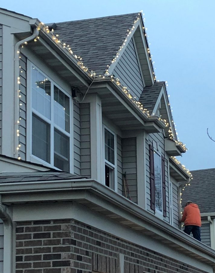 A Plainfield resident puts up lights around his house in November