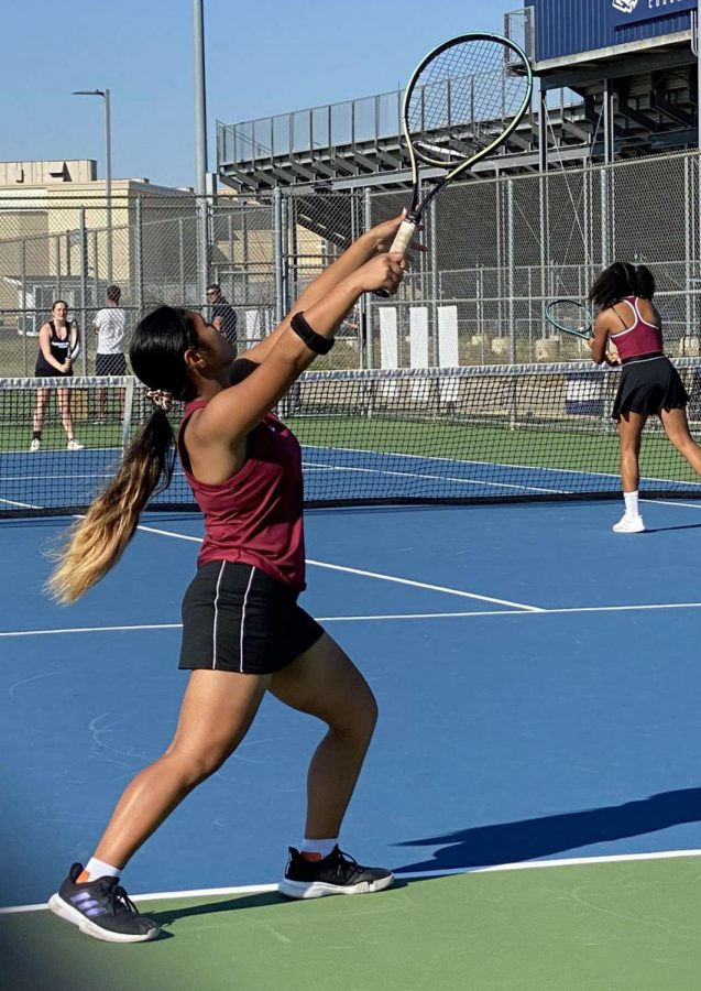 Salcedo serves the ball in a doubles match against Plainfield South. Photo by Adrian Songco
